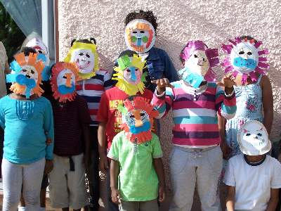 kids wearing paper plate lion masks